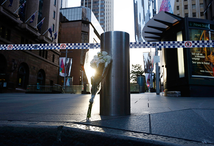 A bouquet is pictured under police tape near the cordoned-off scene of a hostage taking at Martin Place after it ended early December 16, 2014 (Reuters / Jason Reed)