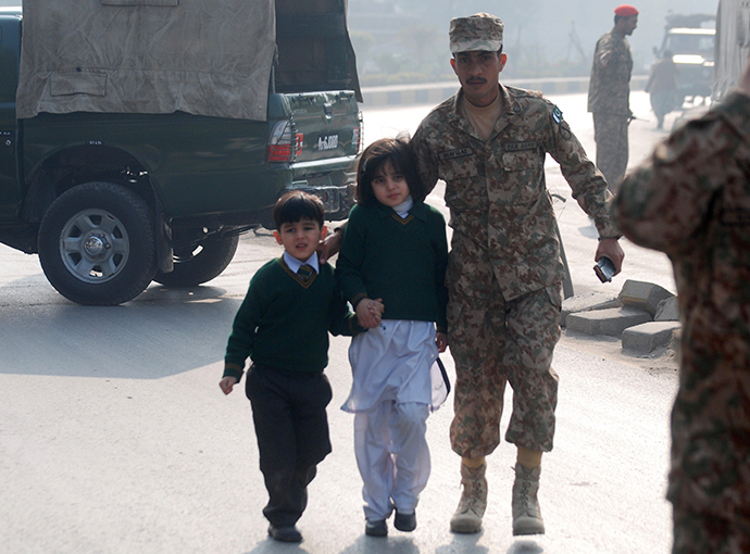 A soldier escorts schoolchildren from the Army Public School that is under attack by Taliban gunmen in Peshawar, December 16, 2014 (Reuters / Khuram Parvez)