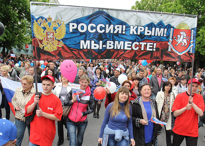 """Participants of the May Day demonstration in Simferopol with a poster reading: """"Russia! Crimea! We are together!"""" (RIA Novosti / Andrey Iglov)"""