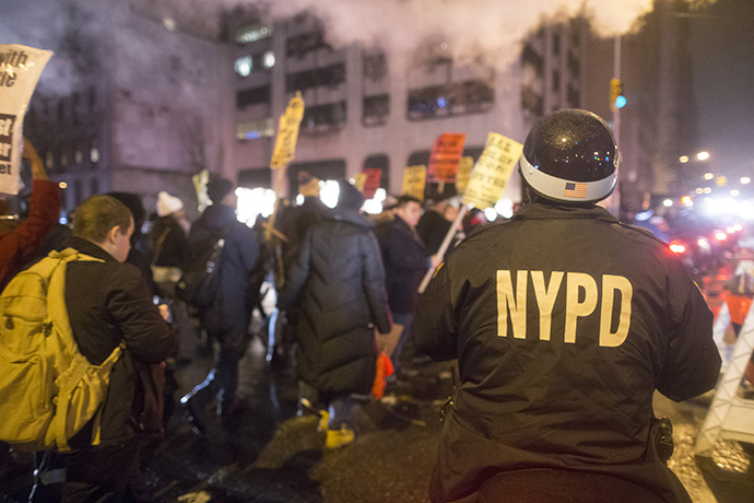 An NYPD Officer on a motorbike keeps track of anti-NYPD protesters as they march through the Upper East Side of Manhattan on December 23, 2014 in New York City (AFP Photo / Michael Graae)