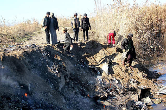 A picture taken on December 24, 2014 reportedly shows Islamic State group fighters collecting pieces from the remains of a Jordanian warplane from the US led coalition after it was shot down in Syria's Raqa region (AFP Photo / STR)