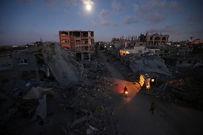 Palestinian pedestrians and a motorcyclist commute along a road between ruins of houses, which witnesses said were damaged or destroyed during the Israeli offensive, in Beit Hanoun town in the northern Gaza Strip (AFP Photo)