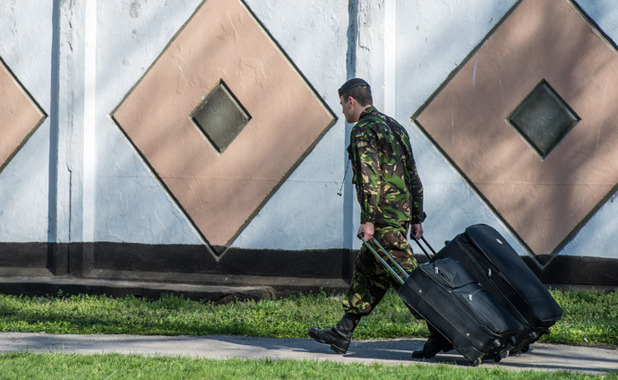 A Ukrainian marine carries their belongings as he leaves his military unit, Ukraine's only marine battalion, in the eastern Crimea's port city of Feodosiya (AFP Photo)