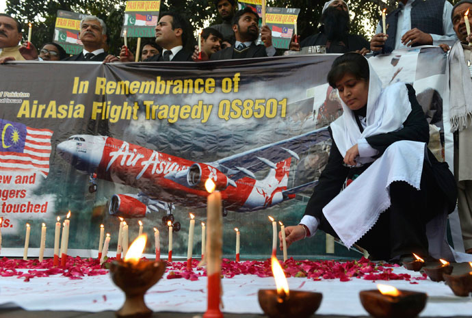 Pakistani civil society activists hold candles during a vigil for the victims of AirAsia Flight 8501 in Lahore on January 2, 2015. (AFP Photo)
