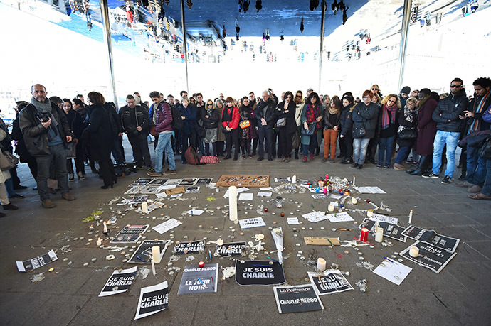 People gather next to signs reading ''I am Charlie'' and candles placed on the ground, after observing a minute of silence in the old Harbor in Marseille on January 8, 2015 for the victims of an attack by armed gunmen on the offices of French satirical newspaper Charlie Hebdo in Paris on January 7 which left 12 people dead. (AFP Photo/Anne-Christine Poujoulat)