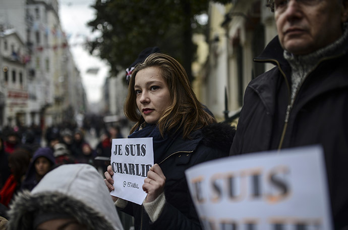 People observe a minute of silence in Istanbul on January 8, 2015 for the victims of an attack by armed gunmen on the offices of French satirical newspaper Charlie Hebdo in Paris on January 7 which left at least 12 dead and many others injured. (AFP Photo/Bulent Kilic)
