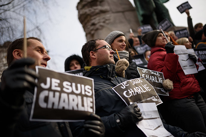 "Slovenian journalists hold pens and placards reading in French ""I am Charlie"" during a gathering in tribute of victims of the attack on French satirical weekly Charlie Hebdo, on January 8, 2015 in Ljubljana, a day after two gunmen killed 12 people in an Islamist attack at Charlie Hebdo's editorial office in Paris. (AFP Photo/Jure Makovec)"
