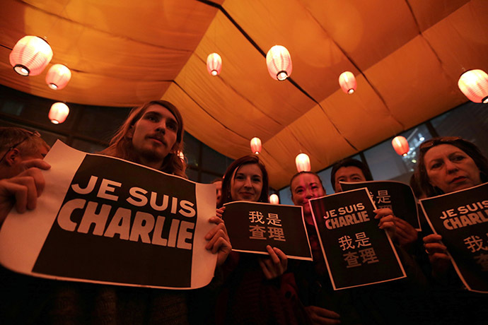 """Foreign journalists and other people hold placards that read """"I am Charlie"""" during a campaign at a bookstore in Beijing January 8, 2015 for the victims of the shooting at the Paris offices of weekly newspaper Charlie Hebdo on Wednesday. (Reuters/Jason Lee)"""