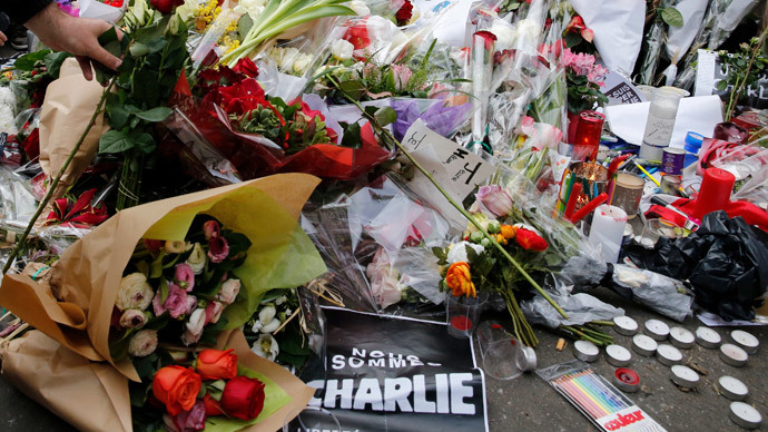 A man places a rose as people continue to pay tribute in front of the offices of the weekly satirical newspaper Charlie Hebdo in Paris January 10, 2015.(Reuters / Pascal Rossignol)