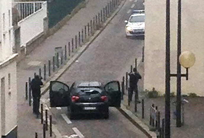 Armed gunmen face police officers near the offices of the French satirical newspaper Charlie Hebdo in Paris on January 7, 2015, during an attack on the offices of the newspaper which left at least 12 dead (AFP Photo / Anne Gelbard)