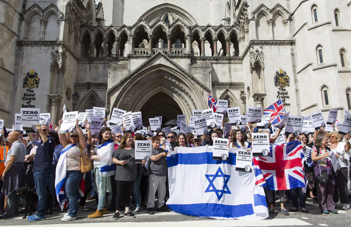 "People hold placards and Israeli and Union flags outide the Royal Courts of Justice as Jewish groups rally in London on August 31, 2014, calling for ""Zero Tolerance for Anti-Semitism"". (AFP Photo/Justin Tallis)"