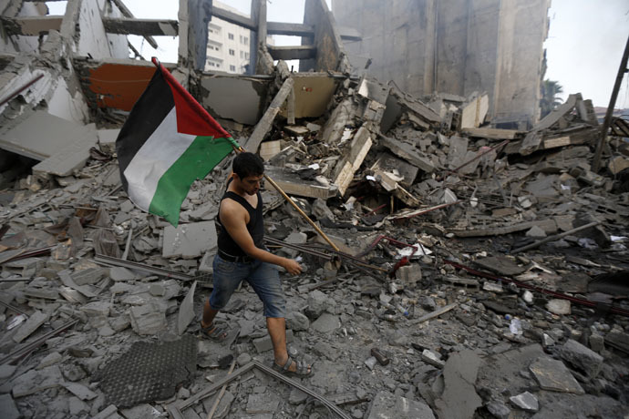 A Palestinian resident carries a national flag as he inspects the remains of Al-Basha, a building that was destroyed by an Israeli air strike in Gaza City (AFP Photo)