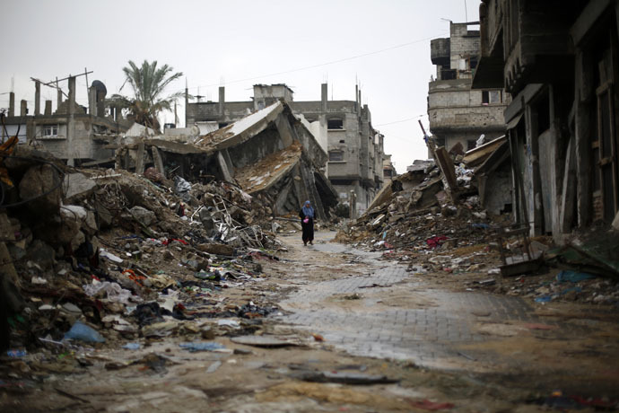 A Palestinian woman walks in the rain past houses that were destroyed during the 50-day Gaza war between Israel and Hamas-led militants (AFP Photo)