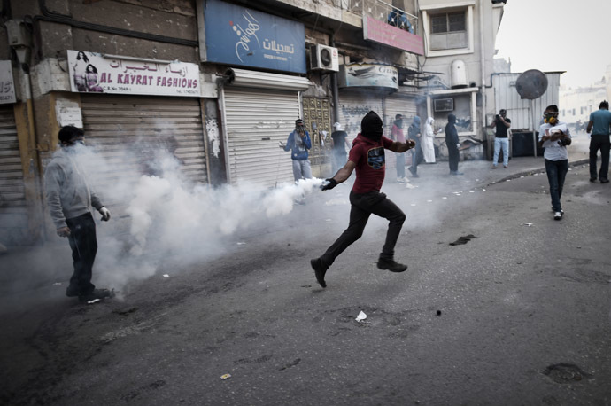 A Bahraini protestor throws back a tear gas canister during clashes with riot police following a protest on January 3, 2015 against the arrest of Sheikh Ali Salman, head of the Shiite opposition movement Al-Wefaq, in Salman's home village of Bilad al-Qadeem, on the outskirts of the capital Manama. (AFP Photo/Mohammed Al-Shaikh)