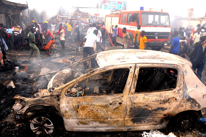 Firefighters and rescuers extinguish a fire at the scene of a bomb blast at Terminus market in the central city of Jos on May 20, 2014. (AFP Photo/Str)