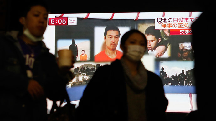 People walk past a TV screen broadcasting a news program about Islamic State hostages Jordanian air force pilot Muath al-Kasaesbeh (back top 3rd L) and Japanese journalist Kenji Goto (back top 2nd L), along a street in Tokyo January 29, 2015.(Reuters / Yuya Shino)