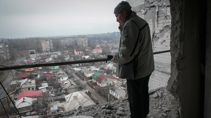 A local in Donetsk standing on a balcony in an apartment block damaged by shelling. (RIA Novosti/Sergey Filatov)