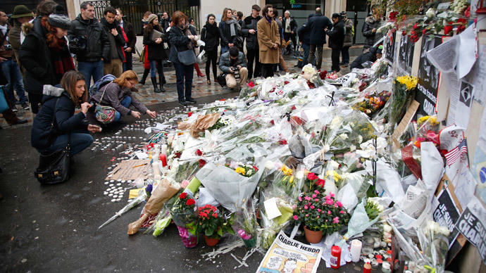 Citizens surround flowers placed near the offices of weekly satirical newspaper Charlie Hebdo in Paris January 9, 2015.(Reuters / Charles Platiau)