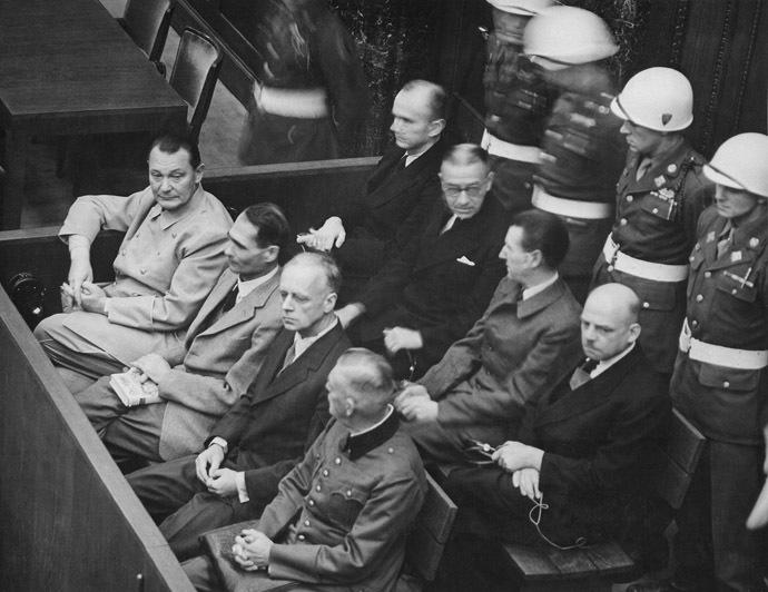 Nuremberg Trials. Defendants in their dock, circa 1945-1946. (in front row, from left to right): Hermann Göring, Rudolf Heß, Joachim von Ribbentrop, Wilhelm Keitel (in second row, from left to right): Karl Dönitz, Erich Raeder, Baldur von Schirach, Fritz Sauckel (Image from Wikipedia)