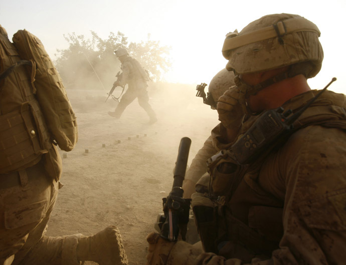 U.S. Marines from Lima company 3rd Battalion 6th Marine Regiment take shelter from the back blast as a Marine fires a law rocket while under fire from Taliban at their patrol base roof in the area of Karez-e-Sayyidi, in Helmand province, April 5, 2010. (Reuters/Asmaa Waguih)