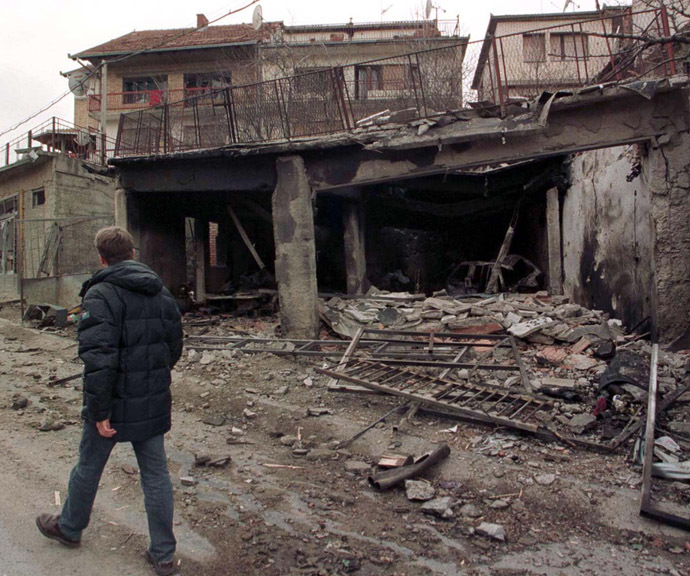 A man passes destroyed houses in Pristina as NATO air strikes continue March 29, 1999. (Reuters)