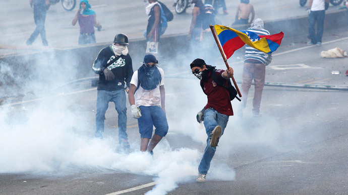 An anti-government protester, with the Venezuelan flag, kicks back a gas canister to police during a demonstration in which masked youths battled police and blocked a main highway in Caracas.(Reuters / Christian Veron)