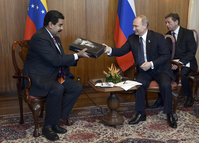 Russia's President Vladimir Putin (2nd R) presents his Venezuelan counterpart Nicolas Maduro with a book dedicated to late Venezuelan President Hugo Chavez during a meeting in Brasilia July 16, 2014. (Reuters/Alexei Nikolskyi/RIA Novosti/Kremlin)