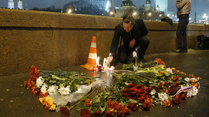 A man places a lit candle at the place where Boris Nemtsov was shot dead near the Kremlin in central Moscow February 28, 2015. (Reuters/Maxim Shemetov)
