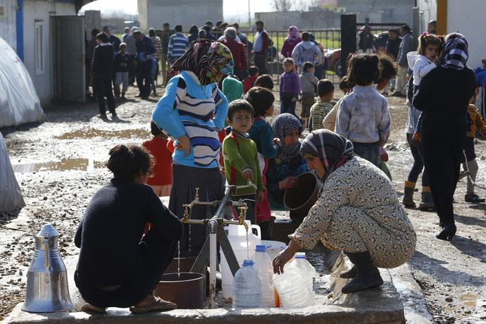 Kurdish refugees from the Syrian town of Kobani wait to fill their jerrycans around a clean water source at a refugee camp in the border town of Suruc, Sanliurfa province February 1, 2015. (Reuters/Umit Bekta)