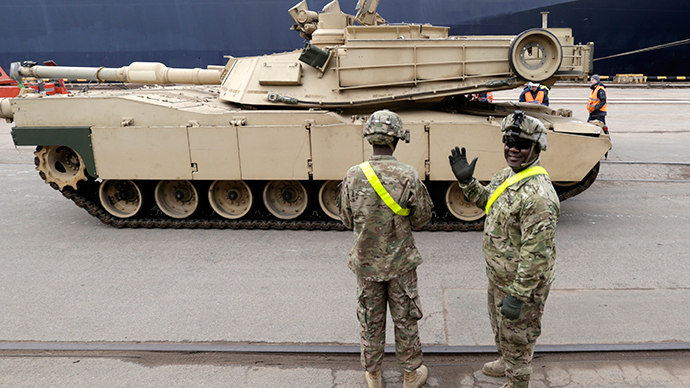 A U.S. soldier greets the media as custom officers inspect an Abrams main battle tank, for U.S. troops deployed in the Baltics as part of NATO's Operation Atlantic Resolve, at Riga port March 9, 2015 (Reuters / Ints Kalnins)