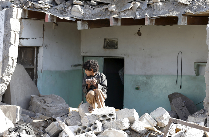 A boy sits at the site of an air strike at a residential area near Sanaa Airport March 26, 2015. (Reuters / Khaled Abdullah)