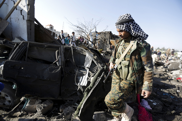 A Houthi fighter walks at the site of an air strike at a residential area near Sanaa Airport March 26, 2015. (Reuters/Khaled Abdullah)