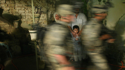 An Iraqi family watches U.S. soldiers in in Baquba early June 28, 2007.  (Reuters/Goran Tomasevic)