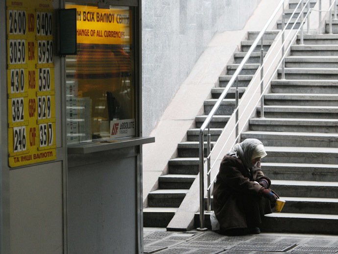 A woman sits next a currency exchange office in Kiev February 26, 2015. (Reuters/Valentyn Ogirenko)
