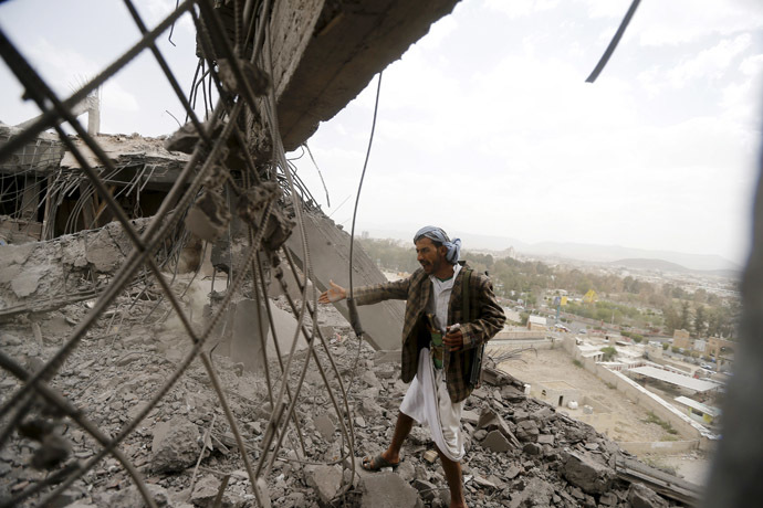 A man reacts as he inspects the damage of a building caused by an air strike in Sanaa April 8, 2015. (Reuters/Khaled Abdullah)