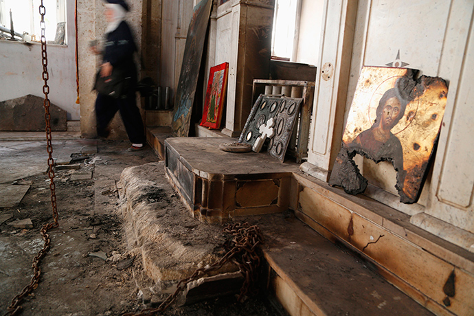 A woman walks inside a damaged church in Maaloula August 21, 2014. Residents of Maaloula, a Christian town in Syria, call on other Christian groups and minorities to stand up to the radicalism that is sweeping across Syria and Iraq (Reuters / Omar Sanadiki)