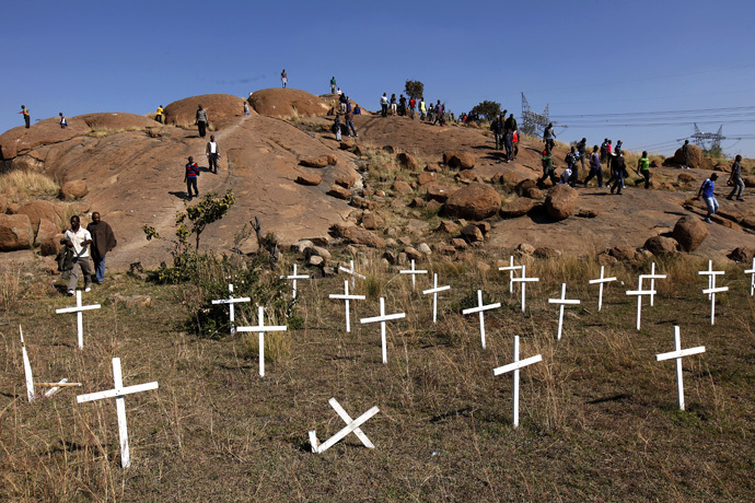 "Members of the mining community walk near crosses placed at a hill known as the ""Hill of Horror"", where 43 miners died during clashes with police last year, during a strike at Lonmin's Marikana platinum mine in Rustenburg, 100 km (62 miles) northwest of Johannesburg, May 14, 2013. (Reuters/Siphiwe Sibeko)"