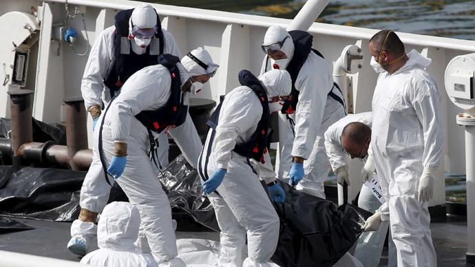 Italian coastguard personnel in protective clothing carry the body of a dead immigrant on their ship Bruno Gregoretti in Senglea, in Valletta's Grand Harbour, April 20, 2015. (Reuters / Darrin Zammit Lupi)