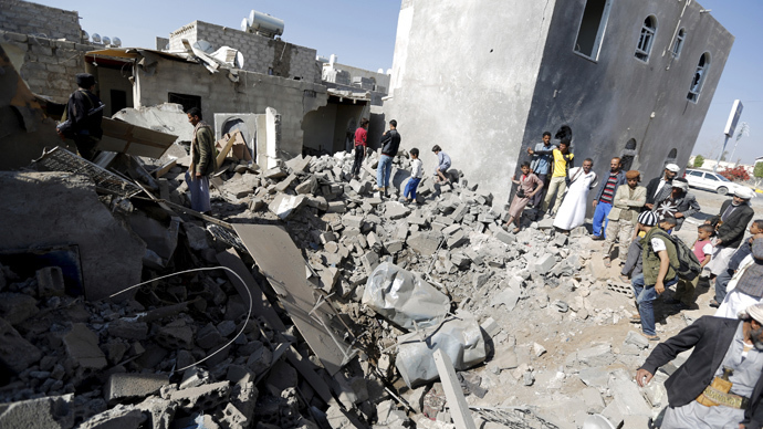 People stand on the rubble of houses destroyed by an air strike near Sanaa Airport (Reuters / Khaled Abdullah)