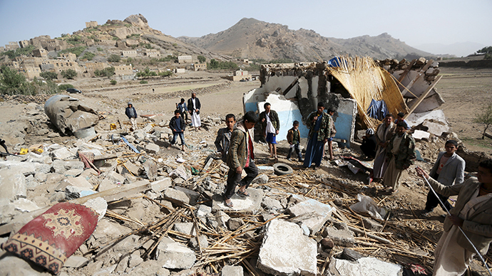 People gather around the wreckage of a house destroyed by an air strike in the Bait Rejal village, west of Yemen's capital Sanaa (Reuters / Khaled Abdullah)