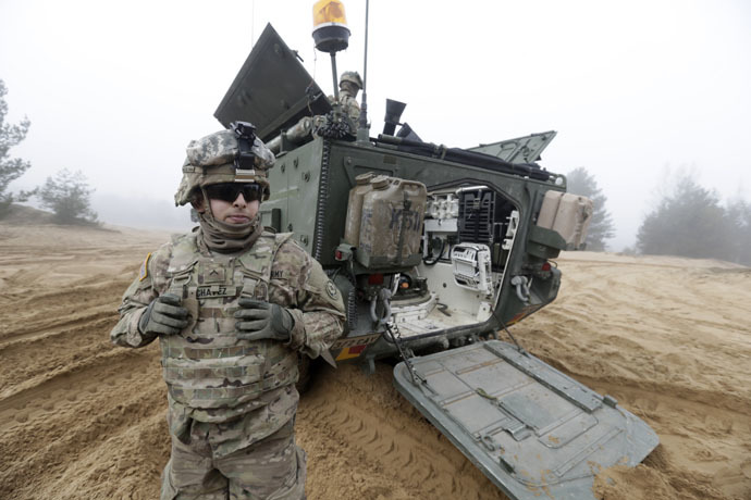 "Soldiers of the U.S. Army's 2nd Cavalry Regiment, deployed in Latvia as part of NATO's Operation Atlantic Resolve, are pictured near their armored vehicle named ""Stryker"" during a joint military exercise in Adazi February 26, 2015. (Reuters/Ints Kalnins)"