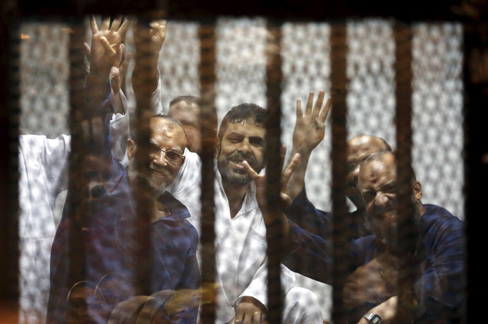 Muslim Brotherhood's senior member Mohamed El-Beltagy (R) and deputy head of the Freedom and Justice Party Essam El-Erian (L) gesture the four-finger Rabia sign from behind bars with other Muslim Brotherhood members at a court in the outskirts of Cairo, April 21, 2015. (Reuters/Amr Abdallah Dalsh)