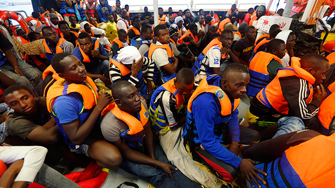 Migrants sit on the deck of the NGO Migrant Offshore Aid Station (MOAS) ship Phoenix after arriving at the port of Pozzallo in Sicily in this handout photo provided by MOAS (Reuters / Darrin Zammit Lupi)