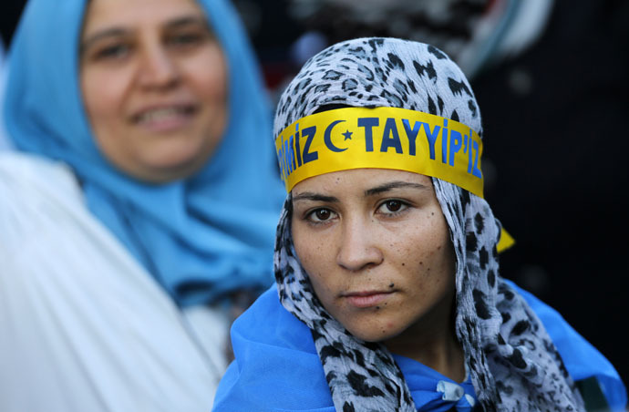 "A supporter of Turkey's Prime Minister and presidential candidate Tayyip Erdogan wears a head band that reads ""We are all Tayyip"" during an election rally in Ankara August 8, 2014. (Reuters/Umit Bektas)"