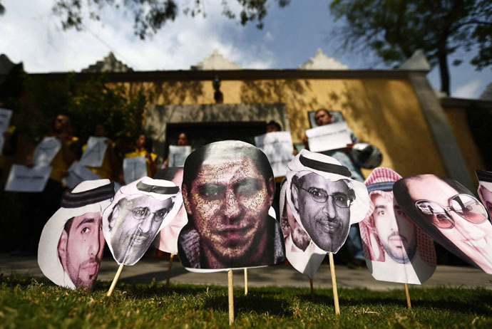A picture of Saudi blogger Raif Badawi (C) is seen between others photos of prisoners in Saudi Arabia during a demonstration for his release from jail outside the Embassy of Saudi Arabia in Mexico City, February 20, 2015. (Reuters/Edgard Garrido)