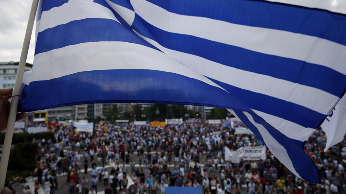 A protester waves a Greek flag during an anti-austerity pro-government rally in front of the parliament building in Athens, Greece, June 21, 2015. (Reuters / Yannis Behrakis)