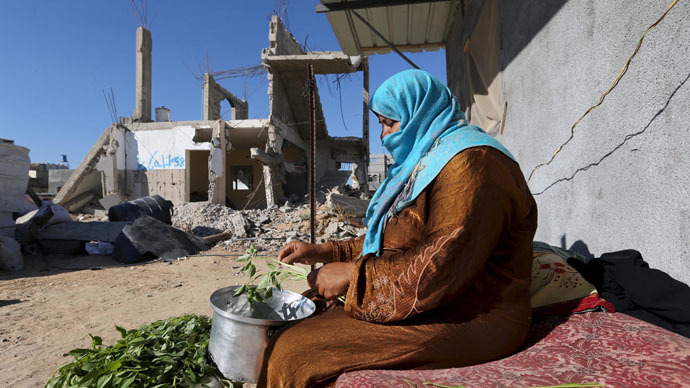 A Palestinian woman prepares food near the wreckage of her house that witnesses said was destroyed by Israeli shelling during a 50-day war last summer, in Khan Younis in the southern Gaza Strip June 22, 2015. (Reuters/Ibraheem Abu Mustafa)
