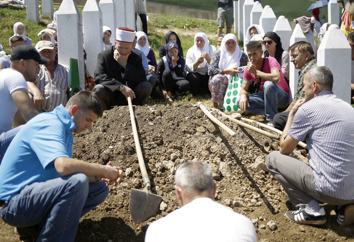 People sit around a grave during a burial at the Memorial Center Potocari, near Srebrenica, Bosnia and Herzegovina July 11, 2015. (Reuters/Stoyan Nenov)
