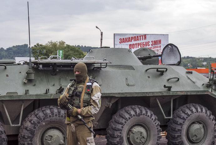 An interior ministry serviceman stands near an armoured personnel carrier (APC) at the scene of a shootout near Mukacheve, Ukraine, July 13, 2015. (Reuters)