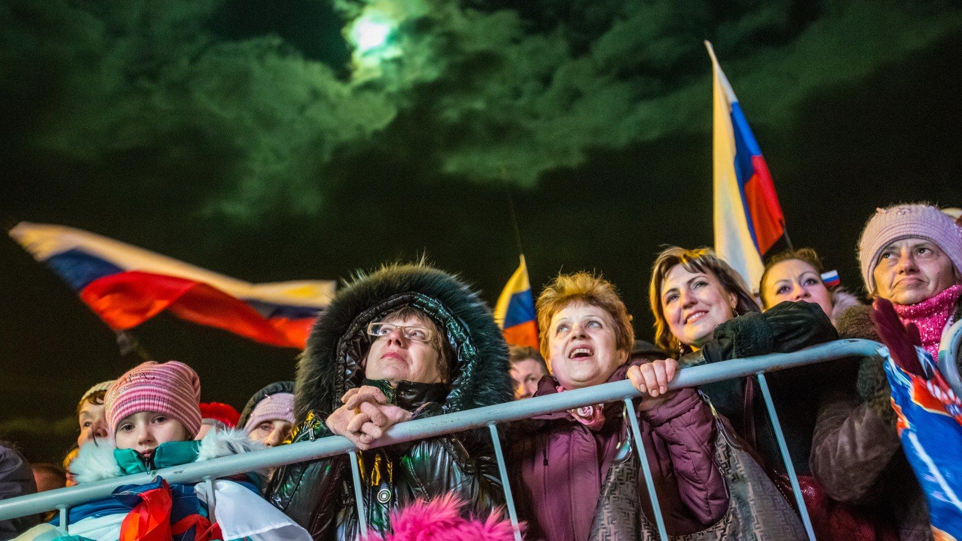 Les habitants de Simferopol regardent le feu d'artifice qui peint le ciel de blanc, bleu et rouge